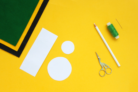 Tutorial how to sew felt leprechaun hat for St. Patrick's day. Concept of DIY sewing art project. Step by step photo instruction. Top view, copy space. Step 1 paper pattern