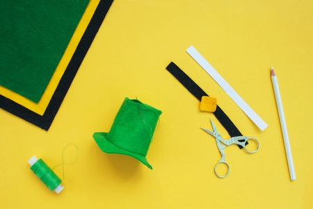 Tutorial how to sew felt leprechaun hat for St. Patricks day. Concept of DIY sewing art project. Step by step photo instruction. Top view, copy space. Step 5 sew the top hats, cut out the decoration Imagens