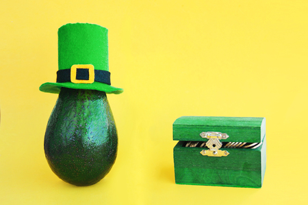St. Patricks day decoration background idea with fresh green avocado in leprechaun hat, wooden open chest with gold coins on bright yellow background. Card concept. Closeup. Front view. Copy space Stok Fotoğraf