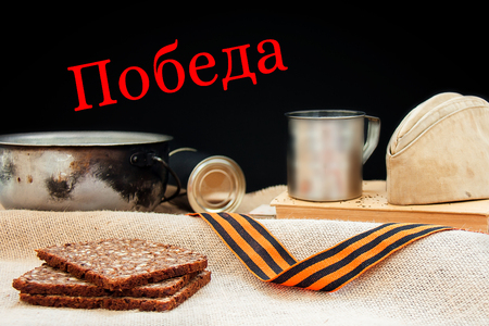 Rations and things of the soldier, symbols of the victory of Soviet army in the Second World War, the Russian military in armed conflicts. 9 May, 23 February card concept. Victory - translation. Stock Photo