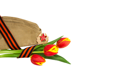 Bouquet of red and yellow tulips entwined with St. George ribbon near the wwii soldier cap. Isolated on white background. 9 May, 23 February card concept. Copy space for text inscriptions. Web banner Foto de archivo