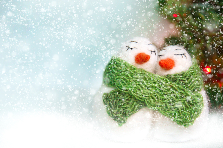 Family of white happy loving felted wool snowmen with green knitted scarf near Christmas tree with lights on bright blue background. Front view. Christmas concept Stock Photo