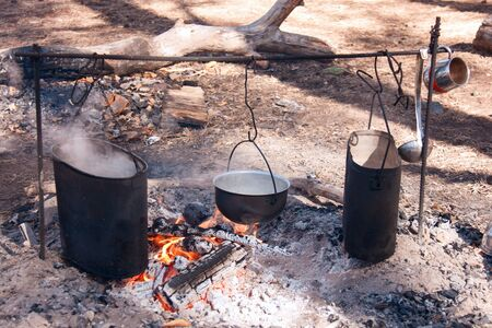 Cooking on the fire diluted in the woods on a camping pot, boiling water, an open flame on charcoal. Smoked walls of dishes in soot. Different forms of hiking bowlers. Stock Photo