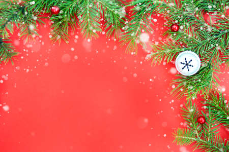 Christmas decoration background with fresh natural branches of Christmas tree spruce on red paper background. Card concept. Closeup. Top view. Flat lay. Copy space