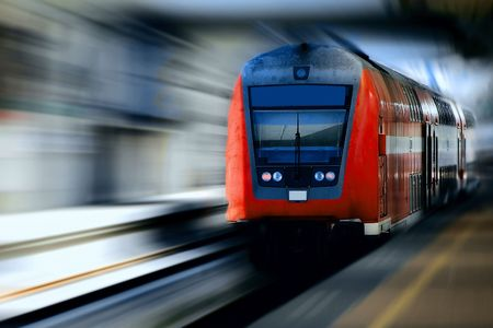 Fast moving red train against a blurred background. Stock Photo