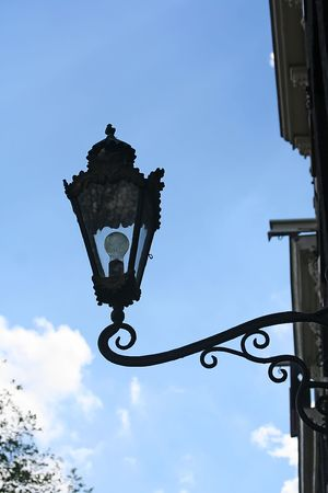 Old style street lamp mounted on a  wall photo