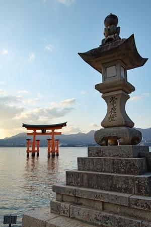 Gate (torii) and stone lantern of the Itsukushima Shrine on Miyajima Island across the bay from Hiroshima in Japan.