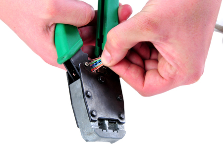 troubleshoot: Cutting an utp cable with a network tool isolated on white backg
