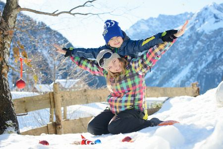 Happy family is playing outside in a Alpine village photo