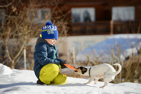 A little boy is playing with a dog on the snow outside photo