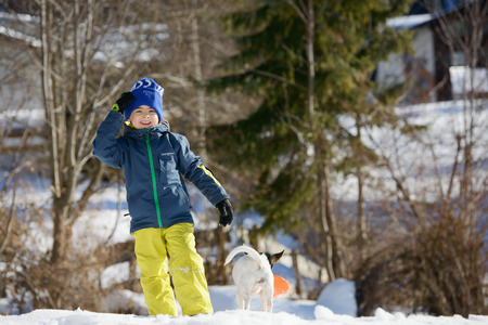 A boy is looking straight staying on a snowy slope in an Austrian village photo
