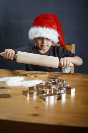 galletas de jengibre: El peque�o ni�o est� horneando galletas de jengibre de Navidad