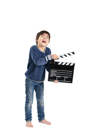 filmmaker: A bare-feet boy laughing keeping clapperboard