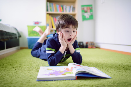 discovering: urprised boy is discovering something from the book