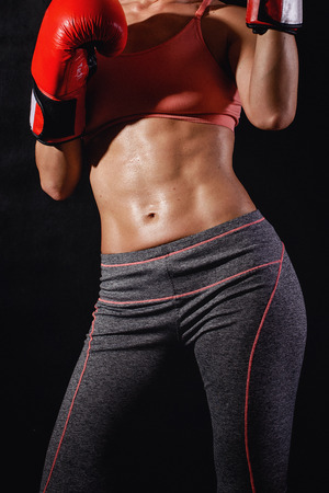 six pack: Strong muscular female body with six pack and with boxing gloves on a black background
