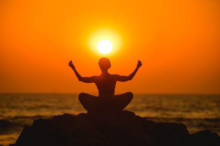 meditates: Female meditates during yoga in the sunset Stock Photo