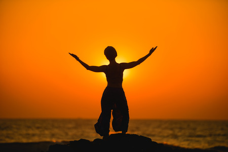 astral: Female meditates during yoga and opens her body to the sun at a sunset