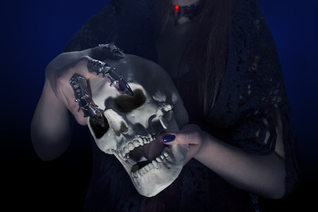 Womans hands with steel fingertips on holding a human skull photo. Stock Photo