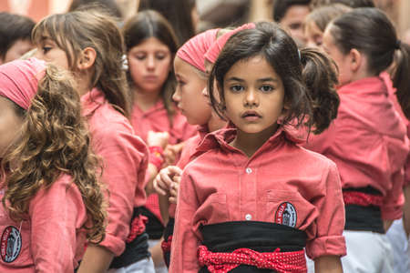 Valls, Spain - October 25, 2015: Portait of a girl during a human tower performance in Santa Ursula's Festival. A castell is a human tower built traditionally in festivals in Catalonia. Editorial