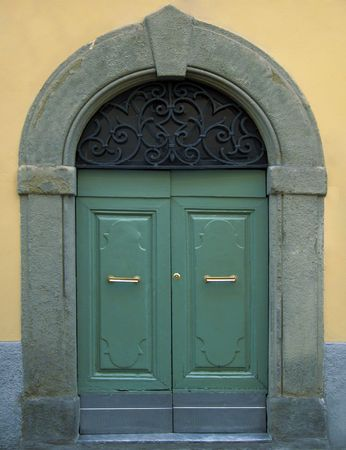 Traditional Wooden Italian Door with Stone Frame and Brass Handles Stock Photo