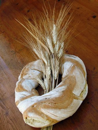 Ring Shaped Loaf of Italian Bread with Wheat Sheaf on a Wooden Table Top photo