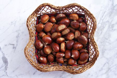 Wicker Basket of Chestnuts on a Marble Table Top