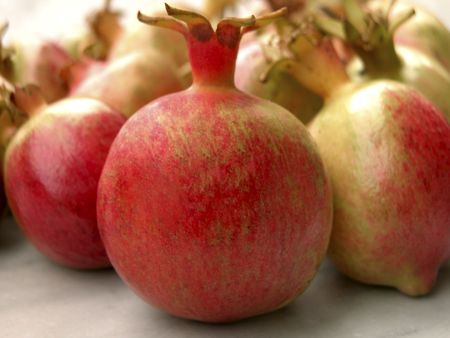 Closeup of a pomegranate fruit in the foreground with more pomegranates fading out of focus in the background Stock Photo
