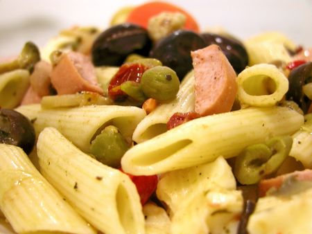 Italian cold salad of pasta quills seasoned with olive oil and garnished with a mix of green and black olives, capers, dried tomatoes, sausage slices and carrots