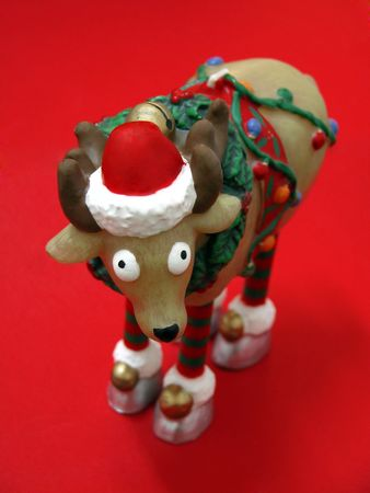 Christmas reindeer with Santa Claus hat on red background