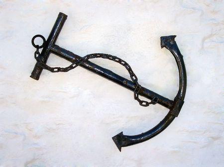 Black iron anchor against a white wall Stock Photo