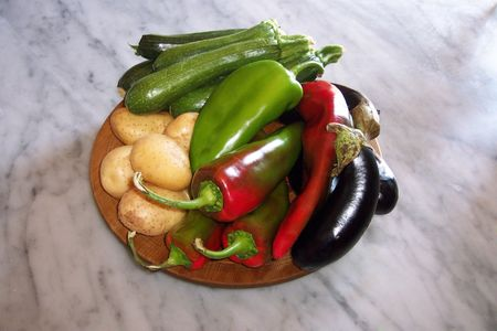 Mixed platter of fresh raw vegetables:  potatoes, zucchini, eggplants, green and red peppers