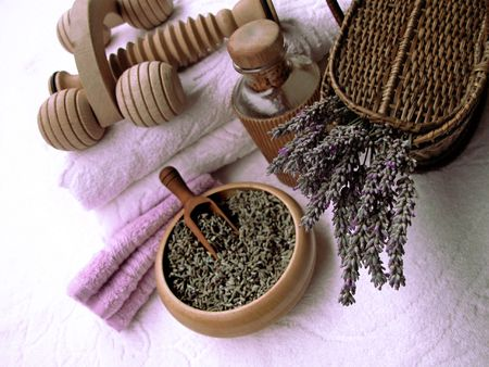 Beauty and body care products in soft lilac hues on a white cotton towel: composition with lavender flowers in a wicker basket, bottle of relaxing essential oil, fluffy towels and wooden  tools photo