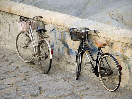 parked: Fietsen Twee oude Nederlandse ouderwetse stijl dames met manden tegen een stenen muur in Bordighera geparkeerd op de Italiaanse Riviera