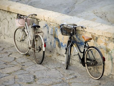 Two old fashioned Dutch style ladies bikes with baskets parked against a stone wall in Bordighera on the Italian Riviera