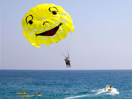 Sport activity - Couple parasailing with yellow smiley parasail over Mediterranean Sea on clear blue day