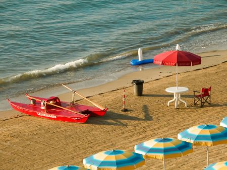 Early morning seaside scene with umbrellas and red lifeguard rescue boat on an Italian Beach
