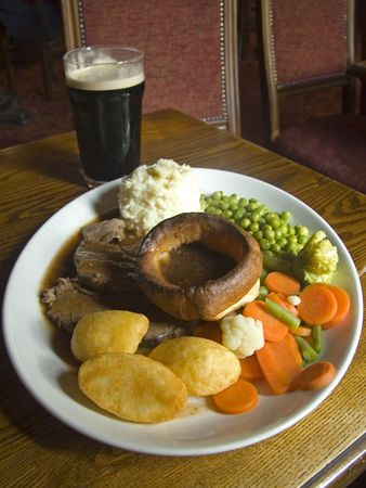 Traditional Sunday roast Dinner with beef, trimmings and glass of stout beer on a wooden table in English pub