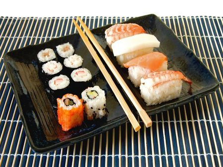 Healthy Japanese sushi meal with assorted maki rolls and wooden chopsticks on a blue ceramic platter and bamboo mat against a white background