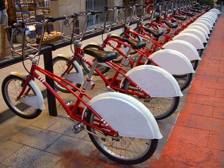 Public bike rental parking point with a neat row of identical red and white bicycles for hire in Barcelona, Spain Stock Photo