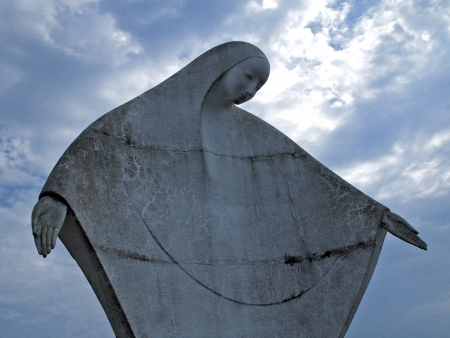Contemporary statue of the Holy Mother in a blessing gesture with her arms outstretched, with an interesting light coming from the clouds in the sky behind her
