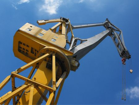 Yellow harbour crane against a blue summer sky