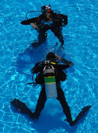 Two scuba divers in full diving gear