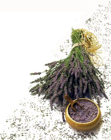 Bunch of lavender flowers tied with a straw ribbon, with dried lavender seeds in a wooden bowl and more scattered seeds in the background. Bottom right corner composition, with plenty of white space for lettering
