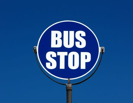tourists stop: Bus stop sign against a blue sky