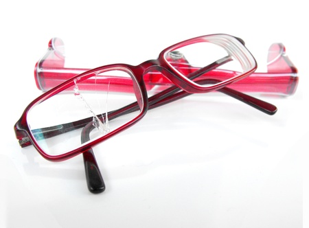 Designer prescription eyeglasses with broken right lens, resting on matching case, isolated on white Stock Photo