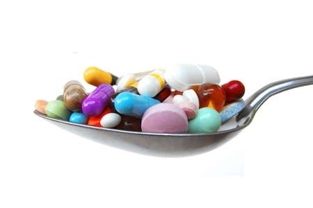 generic medicine: Prescription drug abuse: spoonful of mixed pills, tablets and capsules Stock Photo