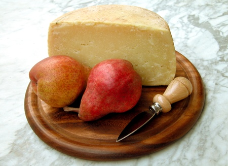 Two Red Pears and a Piece of Cheese on a Wooden Tray Stock Photo