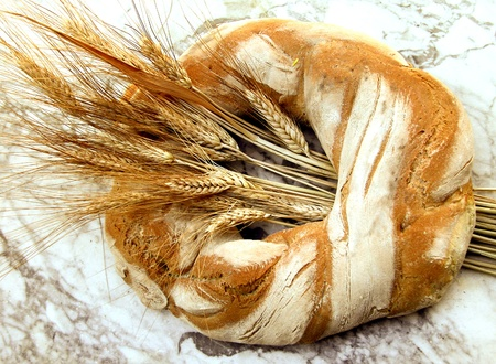 Ring shaped loaf of Italian bread with wheat sheaf on marble table top Imagens
