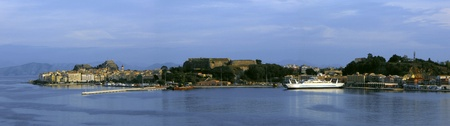 Greek islands, panoramic view of Corfu harbour and old town at sunset as seen from cruise ship leaving port