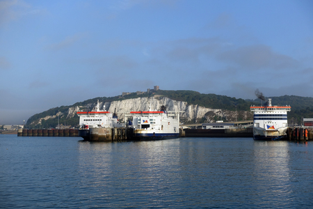 Vehicle and passenger ferries in Dover, UK. White Cliffs and Dover Castle in the background Editorial